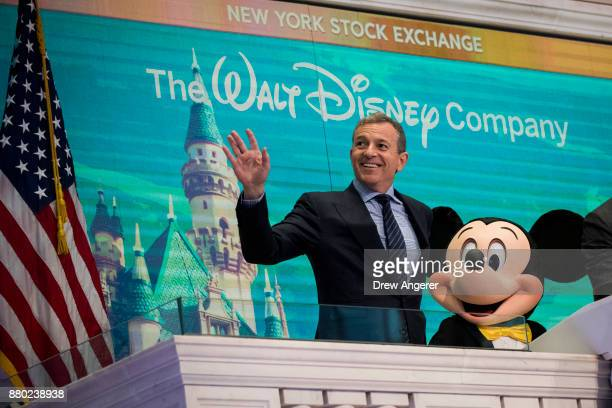 Chief executive officer and chairman of The Walt Disney Company Bob Iger and Mickey Mouse look on before ringing the opening bell at the New York...
