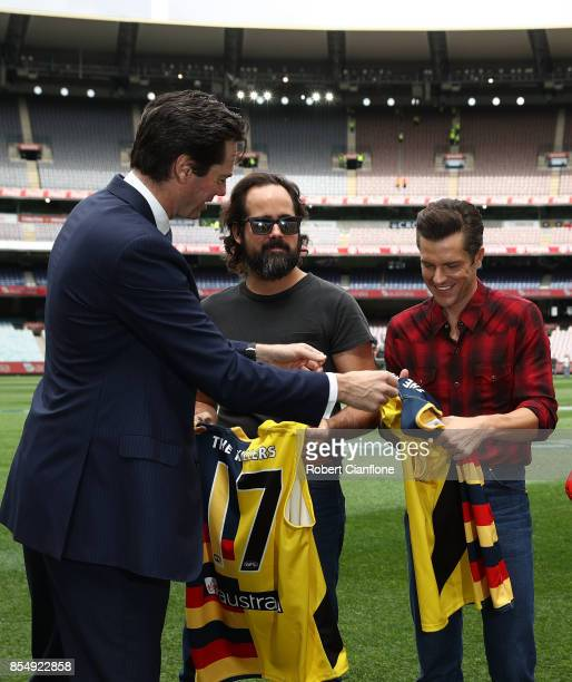 Chief Executive Officer Gillon McLachlan gives Ronnie Vannucci Jr and Brandon Flowers of the Killers an AFL jersey during an AFL Grand Final Press...