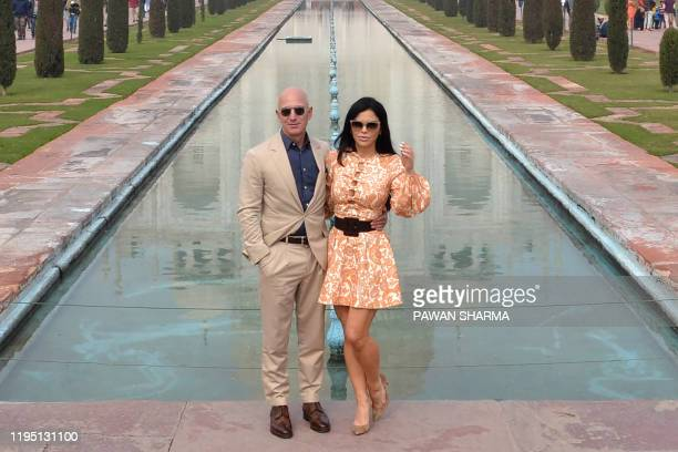 TOPSHOT Chief Executive Officer of Amazon Jeff Bezos and his girlfriend Lauren Sanchez pose for a picture during their visit at the Taj Mahal in Agra...