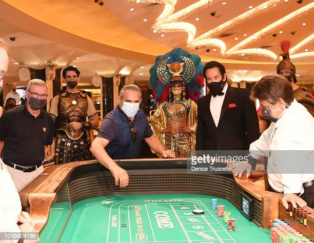 Chief Executive Officer of Caesars Entertainment Tony Rodio and Wayne Newton watch today's first casino customer Ben Laparne roll the dice at the...