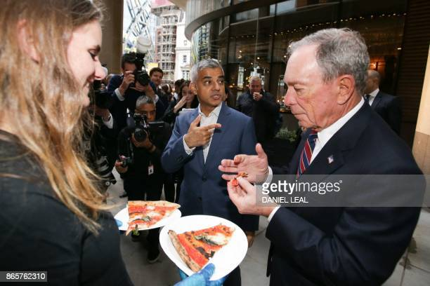 Chief Executive Officer of media company Bloomberg Michael Bloomberg and London Mayor Sadiq Khan try some pizza in the Bloomberg Arcade at the launch...
