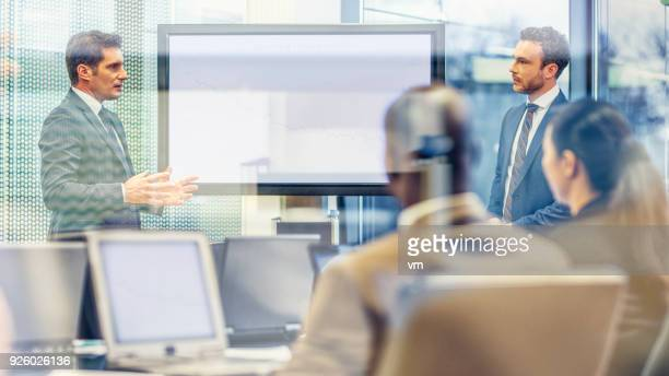 Chief executive talking to financial analyst at a meeting