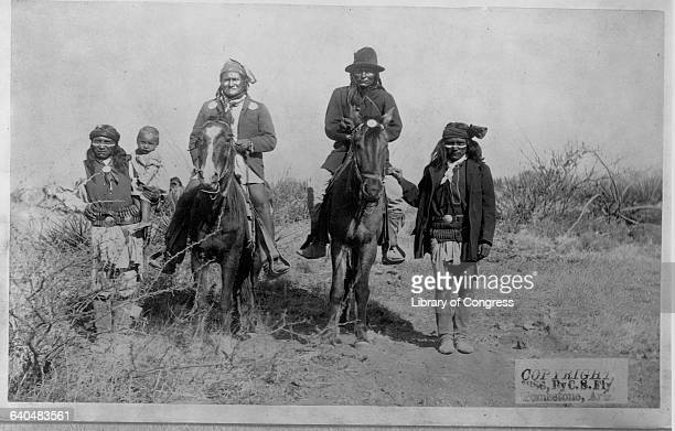 Chief Geronimo the Apache leader who resisted US policy to cosolidate his people onto reservations rides atop a horse with other warriors shortly...