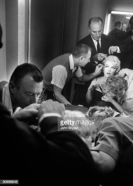 Chief hairdresser for MGM Sydney Guilaroff stylist for the stars combing actress Marilyn Monroe's hair as makeup man works on her eyes in dressing...