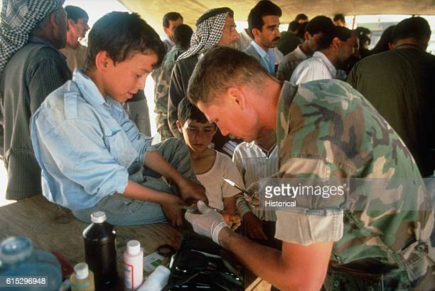 Chief Hospital Corpsman Arthur Angel treats a young Kurdish refugee's blistered foot in a medical clinic on the outskirts of the city The marines and...