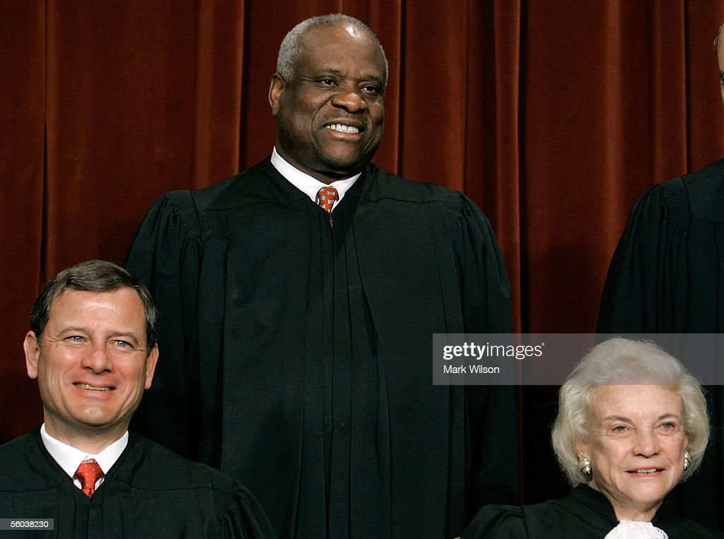 Chief Justice John G. Roberts (L) Justice Clarence Thomas (C) and Justice Sandra Day O'Connor pose for photographers at the U.S. Supreme Court October 31, 2005 in Washington DC. Earlier in the day U.S. President George W. Bush nominated judge Samuel Alito to replace Sandra Day O'Connor who is retiring once her replacement is confirmed by the Senate.