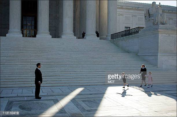 Chief Justice John Roberts waits as his son Jack runs to hug him in front of the Supreme Court building on October 3 2005 At right are Roberts' wife...