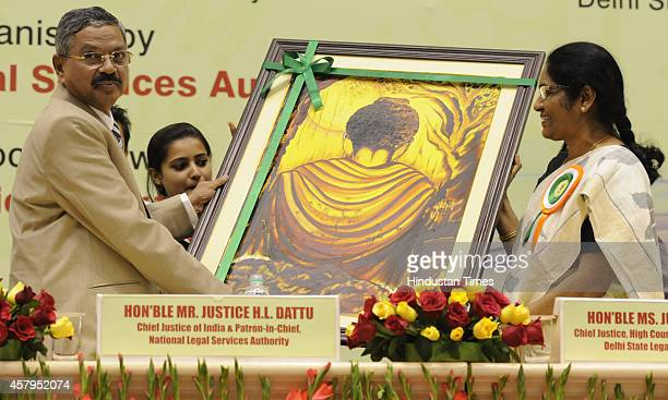 Chief Justice of Delhi High Court G Rohini presents a painting of Budha to the Chief Justice of India Justice HL Dattu during the inauguration of...