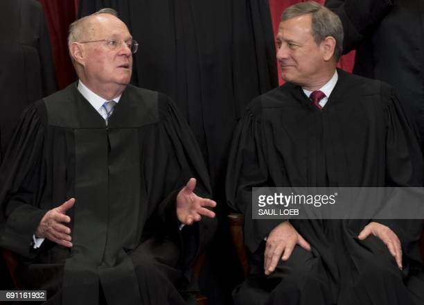Chief Justice of the United States John G Roberts and US Supreme Court Associate Justice Anthony M Kennedy sit for an official photo with other...