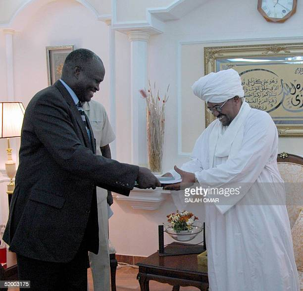 Chief mediator and former Kenyan general Lazaro Sumbeiywo hands Sudanese President Omar alBeshir in Khartoum 17 January 2005 the Arabic and English...
