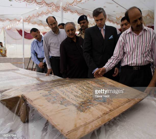 Chief minister of Jammu and Kashmir Omar Abdullah flanked by other dignitaries looks at an oversized centuries old Quranic manuscript at an...