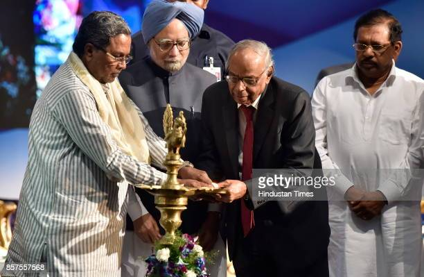 Chief Minister of Karnataka Siddaramaiah former Prime Minister of India Dr Manmohan Singh and C Rangarajan former Governor of RBI light candle during...