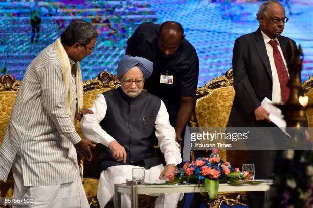 Chief Minister of Karnataka Siddaramaiah helps former Prime Minister of India Dr Manmohan Singh as C Rangarajan former Governor of RBI looks on...