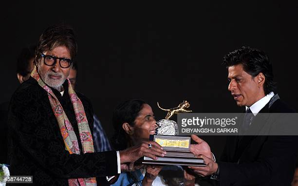 Chief Minister of the eastern state of West Bengal Mamata Banerjee and film actors Amitabh Bachchan and Shah Rukh Khan unveil a trophy during the...