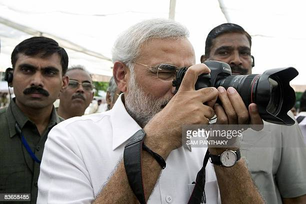 Chief Minister of the Indian state of Gujarat Narendra Modi tries out a camera belonging to a photojournalist during a media interaction at his...
