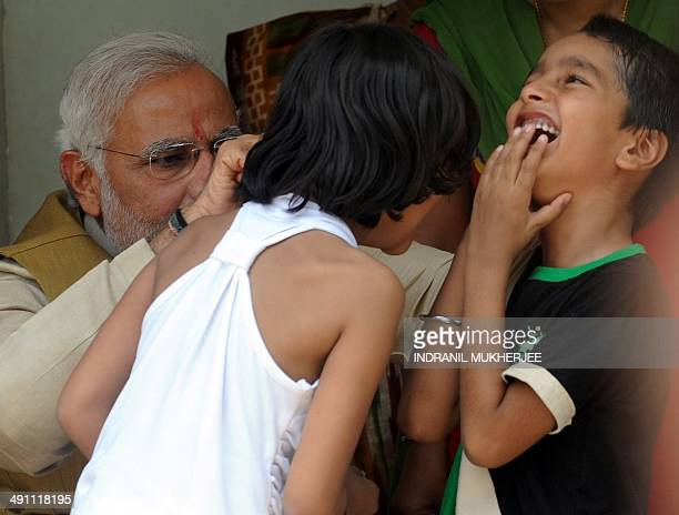 Chief Minister of western Gujarat state and main opposition Bharatiya Janata Party prime ministerial candidate Narendra Modi jokingly pulls the ears...