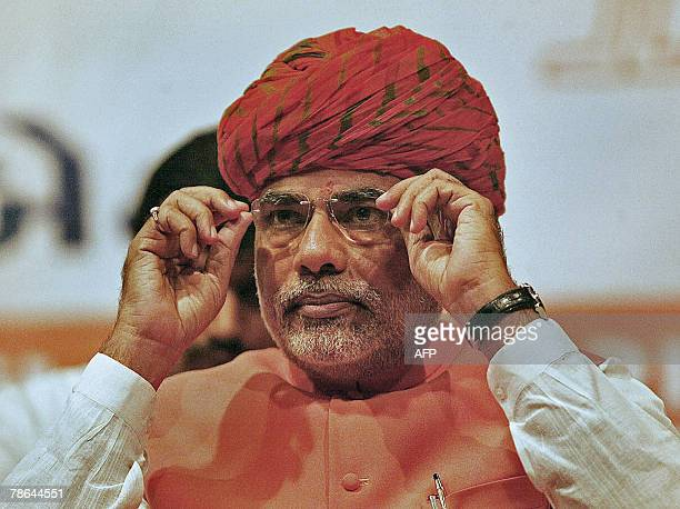 Chief Minister of Western India's Gujarat state Narendra Modi adjusts his spectacles at the Town Hall during the Bhartiya Janta Party's Legislative...