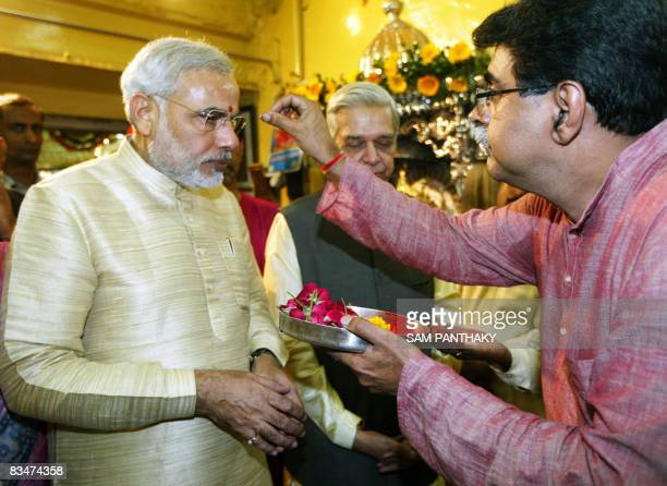 Chief Minister of western India's Gujarat state Narendra Modi receives blessings from Hindu priest Shirish Avasthi at the Bhadrakali temple on the...