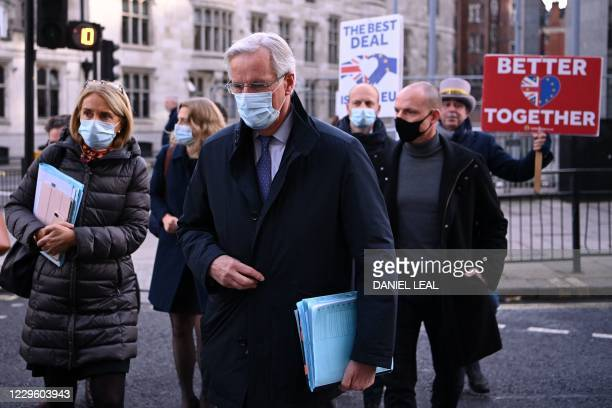 Chief negotiator Michel Barnier wearing a face mask because of the novel coronavirus pandemic, is followed down a street by Anti-Brexit activists as...