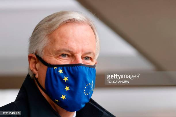 Chief negotiator Michel Barnier wearing a mask because of the novel coronavirus pandemic walks to a conference centre to continue negotiations on a...