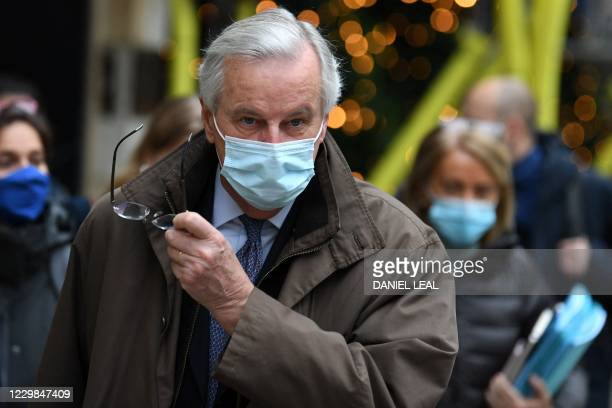 EU chief negotiator Michel Barnier wearing a protective face covering to combat the spread of the coronavirus removes his spectacles as he leaves his...