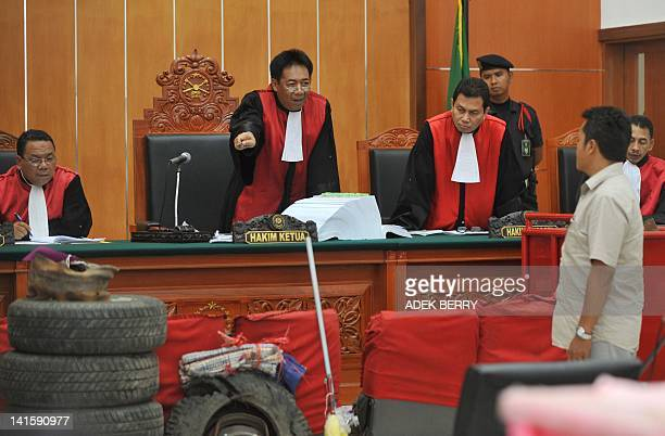 Chief of Judges Encep Yuliardi gestures as he asks witness Djatmiko Bambang victim of Bali attacks about evidences during a trial at the West Jakarta...