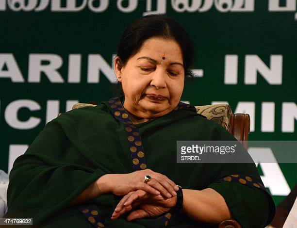 Chief of the All India Anna Dravida Munnetra Kazhagam party Jayalalithaa Jayaram looks at her watch during her swearingin ceremony as the chief...