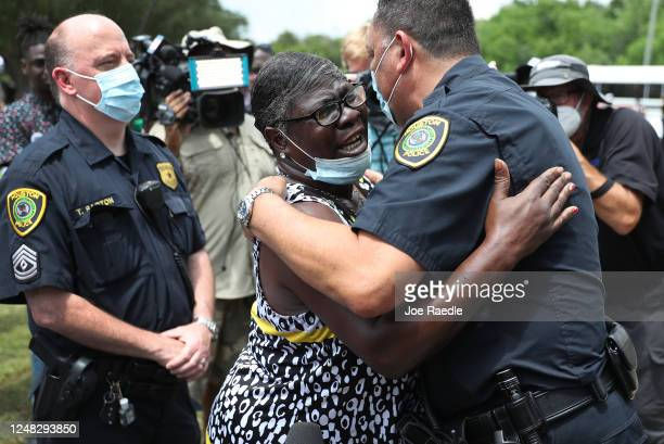 Chief of the Houston Police Department,Art Acevedo, is hugged by Charlene Davis as he visits with people standing in line to attend the public...