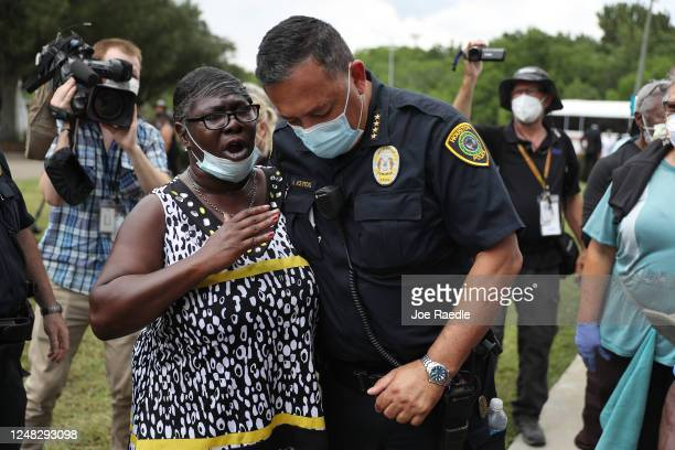 Chief of the Houston Police Department,Art Acevedo, prays with Charlene Davis as he visits with people standing in line to attend the public viewing...