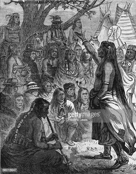 A chief of the North American Comanche Indian tribe addresses his people as they gather amid trees and teepee tents 19th Century