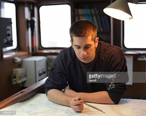 Chief officer planning route on sea chart