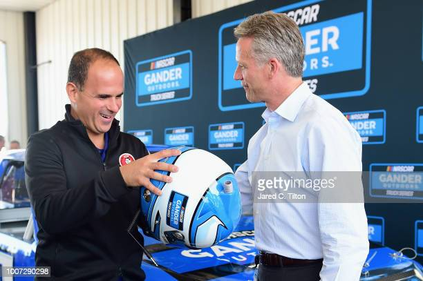 Chief Operating Officer Steve Phelps presents Marcus Lemonis Chairman of Gander Outdoors Camping World and Overton's with a helmet during a press...