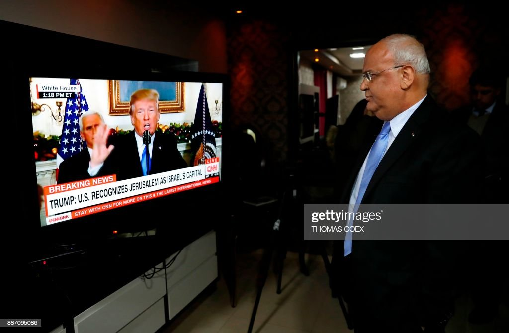 Chief Palestinian negotiator Saeb Erekat watches on TV a speech given by US President Donald Trump at his residence in the West Bank city of Jericho, on December 6, 2017, during which Trump announced the recognition of the disputed city of Jerusalem as Israel's capital and his plans to relocate the US embassy there from its current headquarters in Tel Aviv. Trump's announcement plunges the United States into a decades-long dispute over a city considered holy by Jews, Muslims and Christians, and flies in the face of warnings from US allies and leaders across the Middle East. /