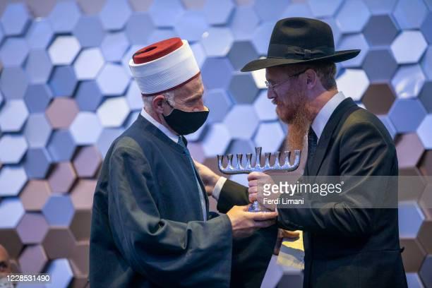 Chief rabbi of Albania Joel Kaplan hands a menorah to a representative of the Kosovar Islamic Community at the Roch Hachanah ceremony organized by...