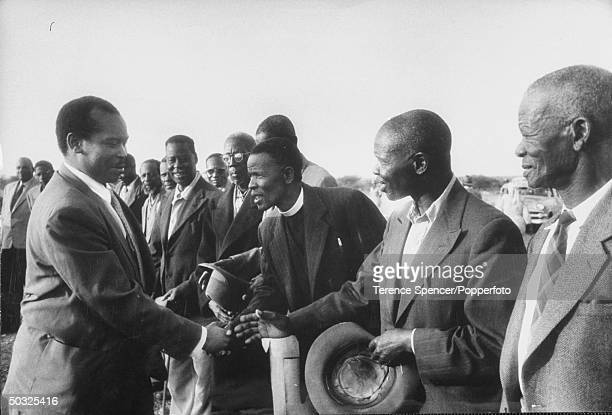 Chief Seretse Khama shaking hands with tribal dignitaries.