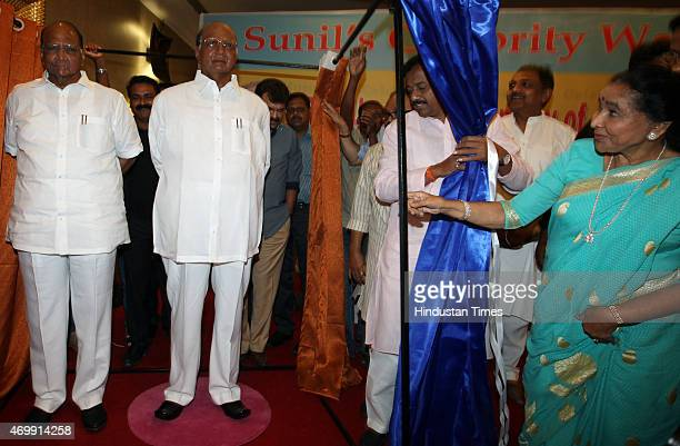 Chief Sharad Pawar poses with his wax statute as legendary singer Asha Bhosle looks on during the unveiling of their wax models at the MCA lounge of...