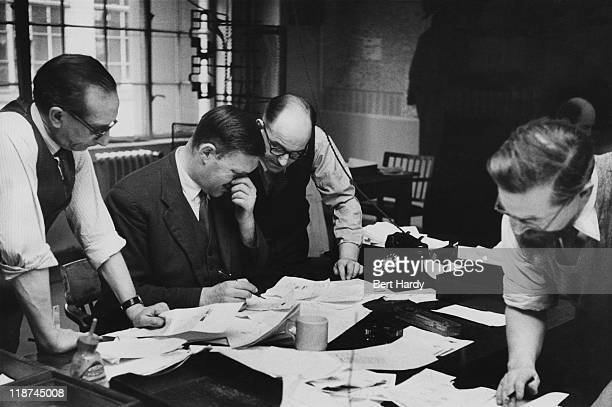 Chief subeditor 'Tiny' Lear answers queries from two of the printing staff on a Saturday afternoon in the newsroom at the News of The World April...