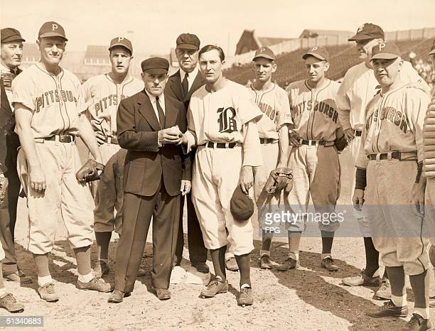Chief umpire Bill Stewart presents a ball to Boston Braves baseball player Paul Waner who made his 3000th career hit in a match against the...