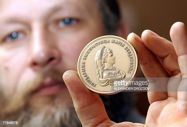 Chief-painter of a mint holds a medal with Russian Empress Maria Fedorovna, the mother of Russia's last czar's image during a presentation in...