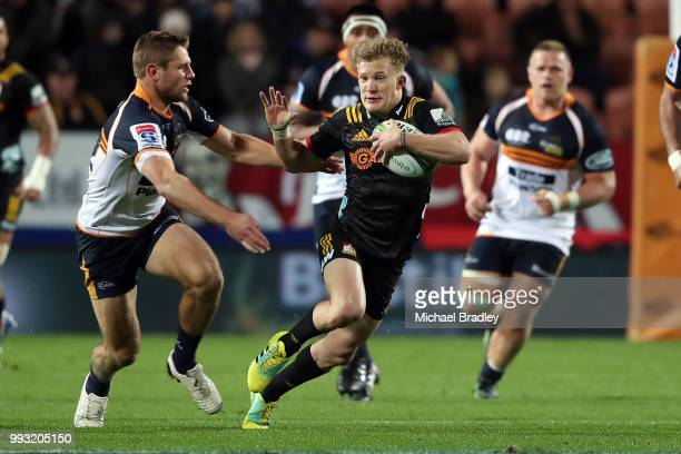 Chiefs Damian McKenzie looks to fend off the tackle during the round 18 Super Rugby match between the Chiefs and the Brumbies at FMG Stadium Waikato...