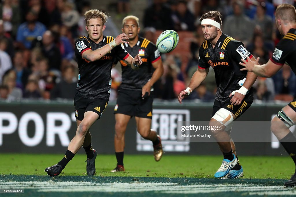 Chiefs Damian McKenzie (L) passes the ball during the round seven Super Rugby match between the Chiefs and the Highlanders at FMG Stadium on March 30, 2018 in Hamilton, New Zealand.