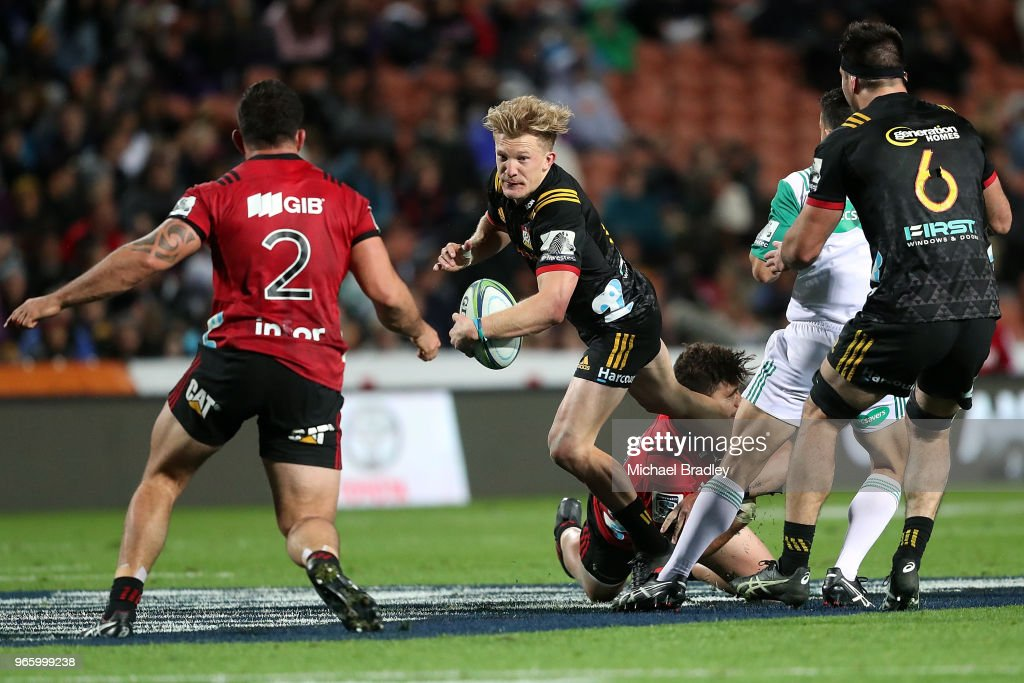 Chiefs first five Damian McKenzie (C) is tackled during the round 16 Super Rugby match between the Chiefs and the Crusaders at Waikato Stadium on June 2, 2018 in Hamilton, New Zealand.