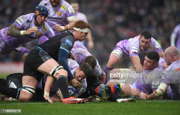 Chiefs player Jonny Hill dives over to score the first Exeter try despite the attentions of Rob Harley of Glasgow during the Heineken Champions Cup...