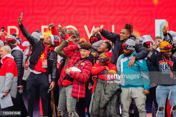 Chiefs players do the tomahawk chop and pose for a photo during the Kansas City Chiefs Victory Parade on February 5 2020 in Kansas City Missouri