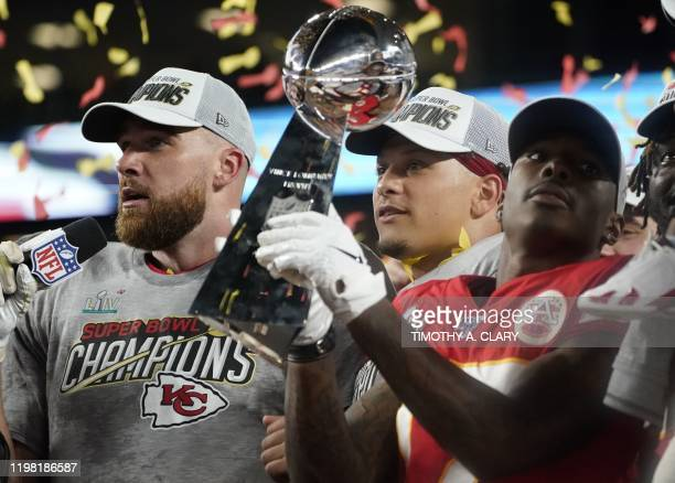 Chiefs Tight End Travis Kelce Quarterback Patrick Mahomes and Wide receiver Mecole Hardman hold the trophy after winning Super Bowl LIV between the...