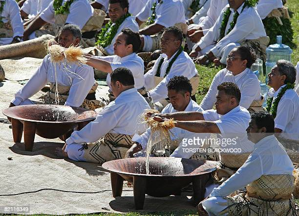 Chiefs use hibiscus bark fibre to strain pounded kava root in carved tanoa bowls for King George Tupou V during the taumafa kava ritual and...