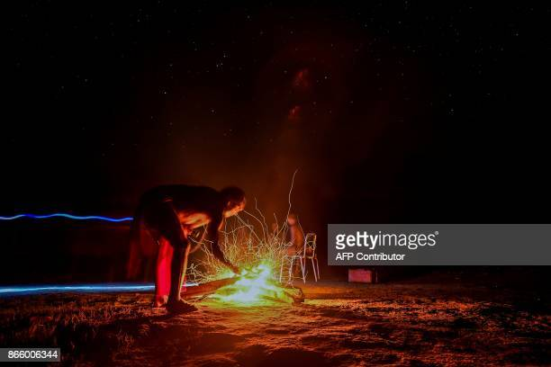 Chieftain Akaupotyr Waiapi sets up a bonfire at the Manilha village in Waiapi indigenous reserve in Amapa state in Brazil on October 12 2017 Tribal...