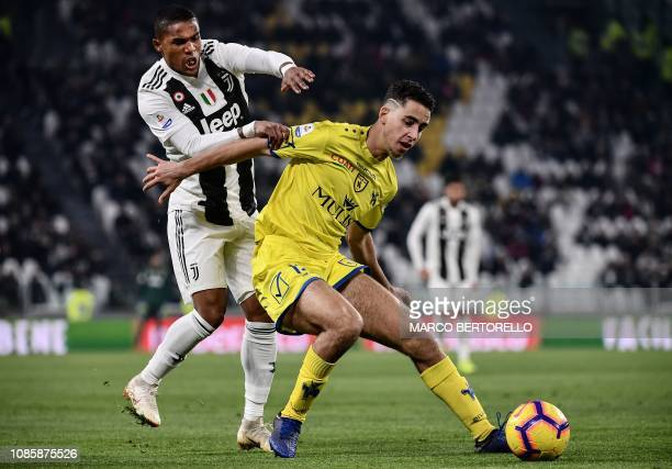 Chievo's Belgian midfielder Sofian Kiyine holds off Juventus' Brazilian forward Douglas Costa during the Italian Serie A football match Juventus vs...