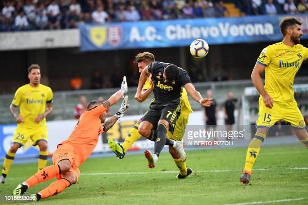 Chievo's goalkeeper Stefano Sorrentino and Juventus' Portuguese forward Cristiano Ronaldo go for the ball during the Italian Serie A football match...