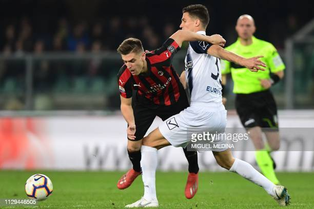 Chievo's Italian defender Marco Andreolli tackles AC Milan's Polish forward Krzysztof Piatek during the Italian Serie A football match Chievo Verona...